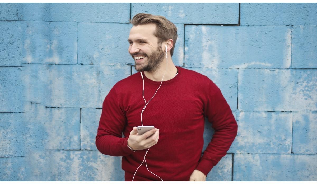jeune homme content avec son smartphone en main et ecouteurs