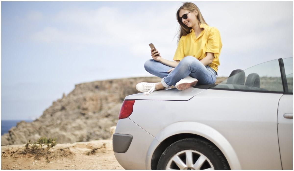 une femme assise sur le capot d'une voiture avec son smartphone en main