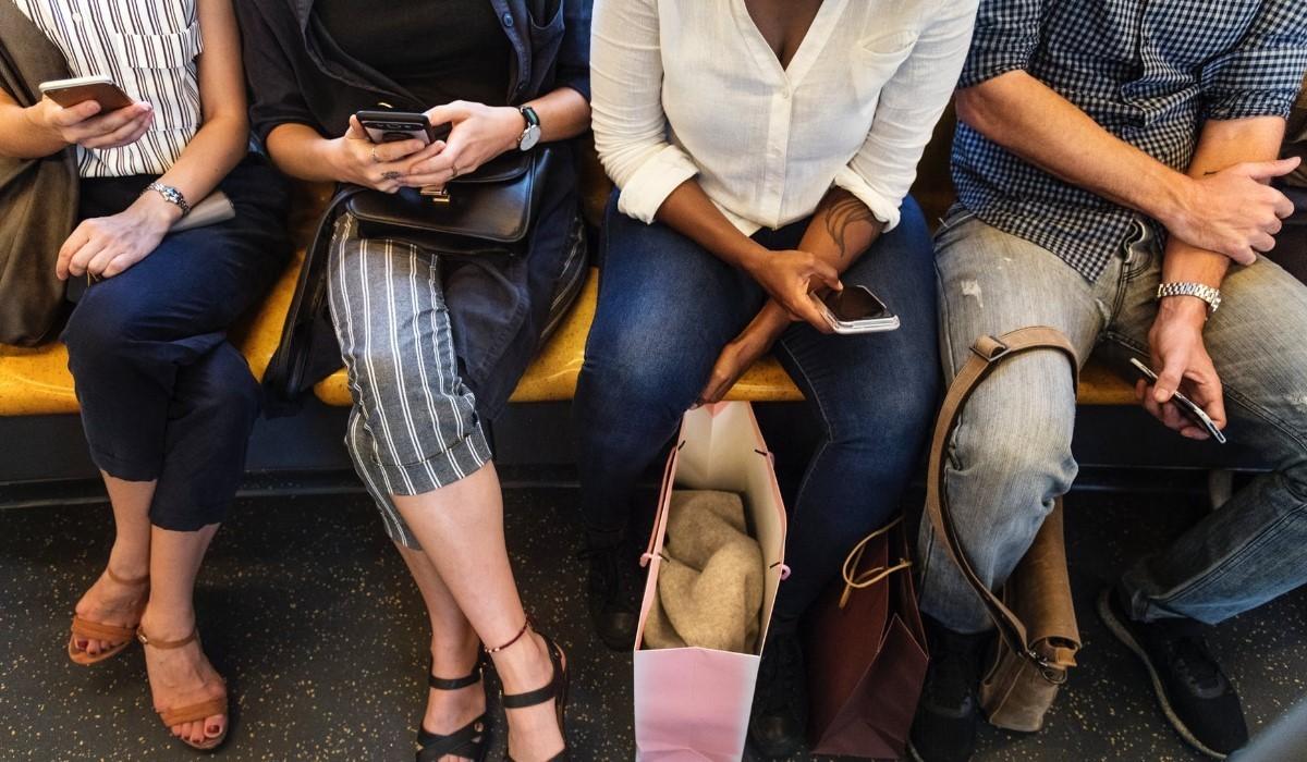 quatre personnes assis avec leur smartphone en main