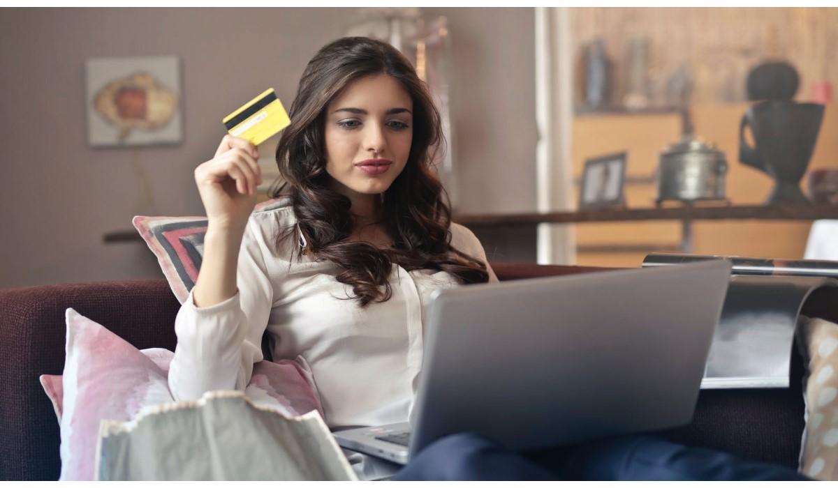 jeune femme avec sa carte bancaire en main face à son pc