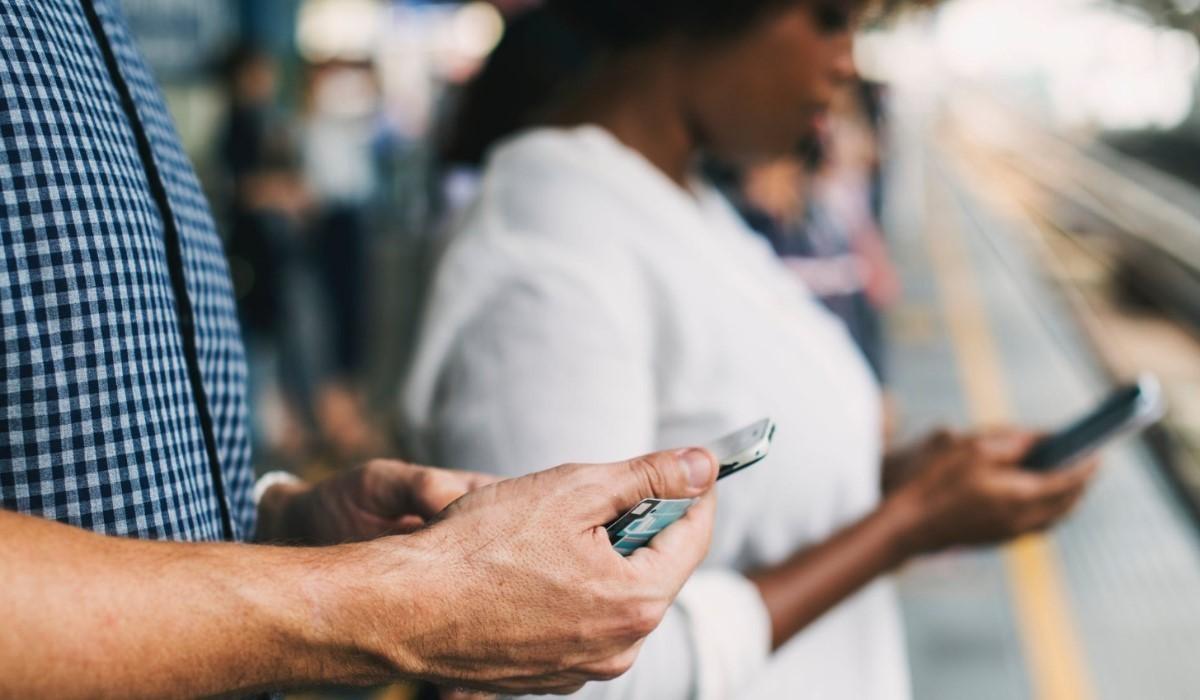 Deux personnes debout qui surfent sur leur smartphone