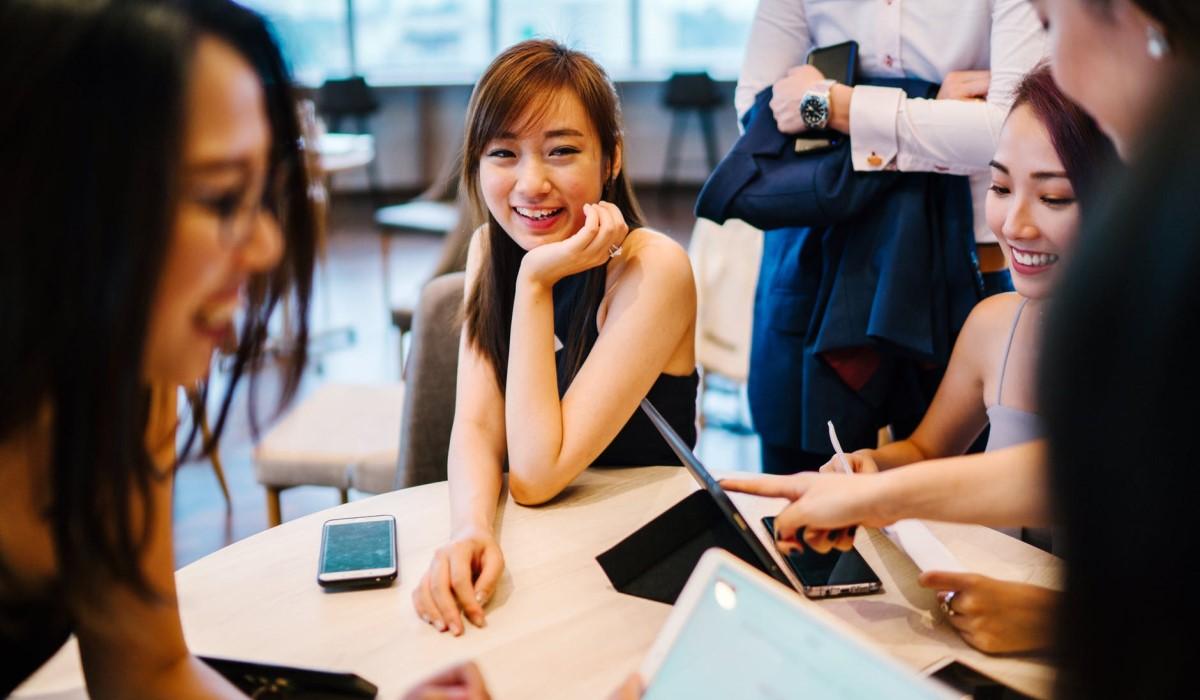 jeunes femmes assises autour d'une table avec leurs smartphone