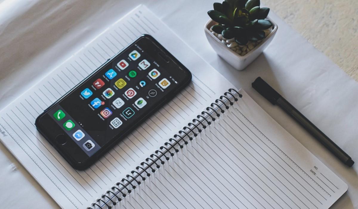 un smartphone pose sur un bloc notes