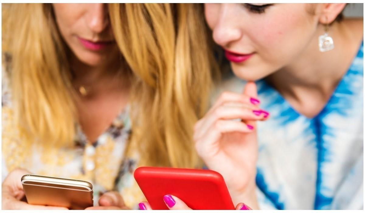 deux jeunes femmes qui surfent sur leur mobile
