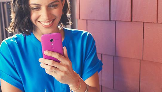 femme sourit avec un smartphone rose