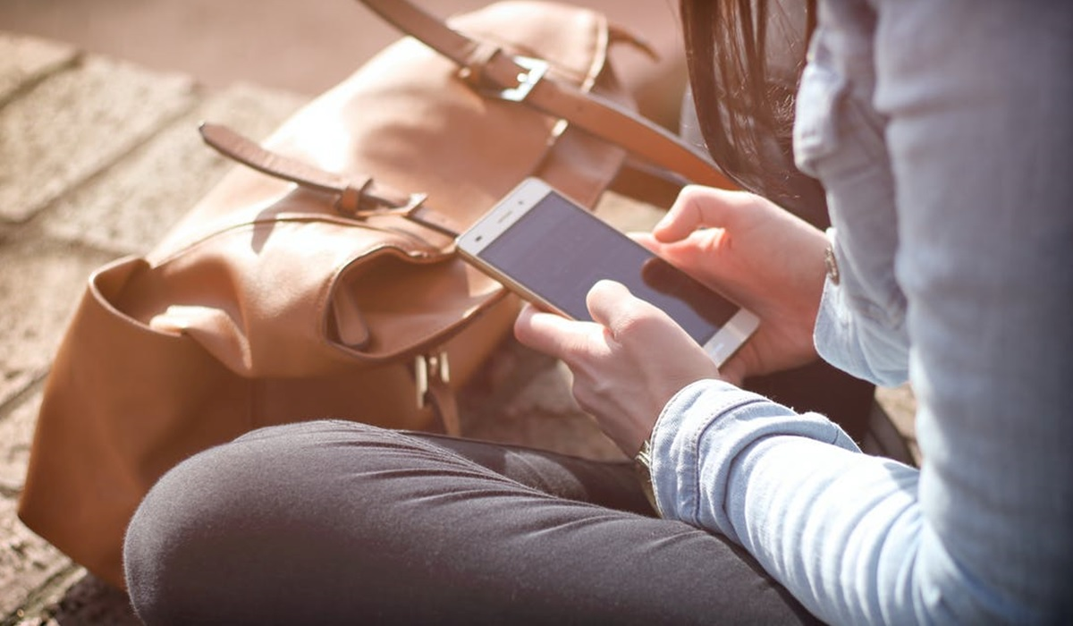 femme assise avec sac à main en train de regarder son téléphone