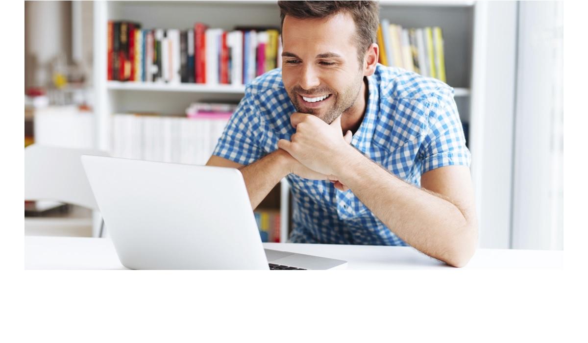 Un homme avec le sourire devant son ordinateur