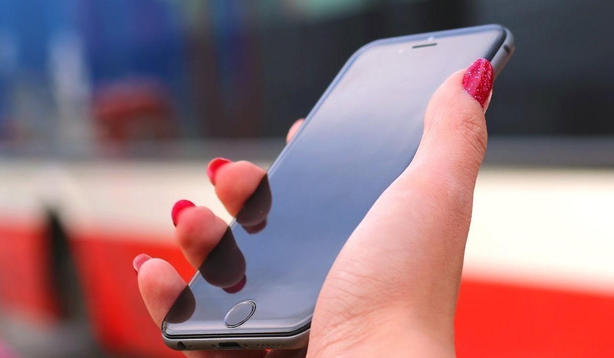 femme qui tient son smartphone dans la main