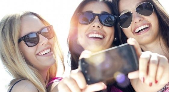 3 jeunes femmes qui se prennent en photo avec un smartphone