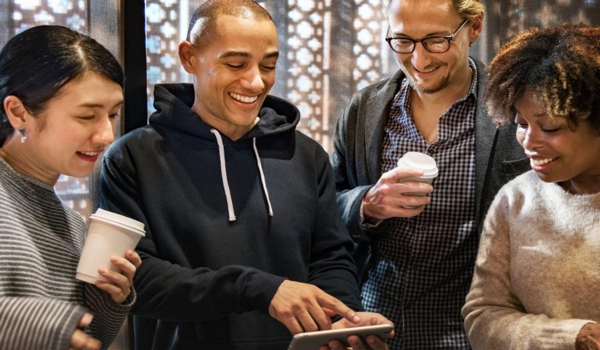 4 personnes qui regardent le Smartphone de l'un d'entre eux