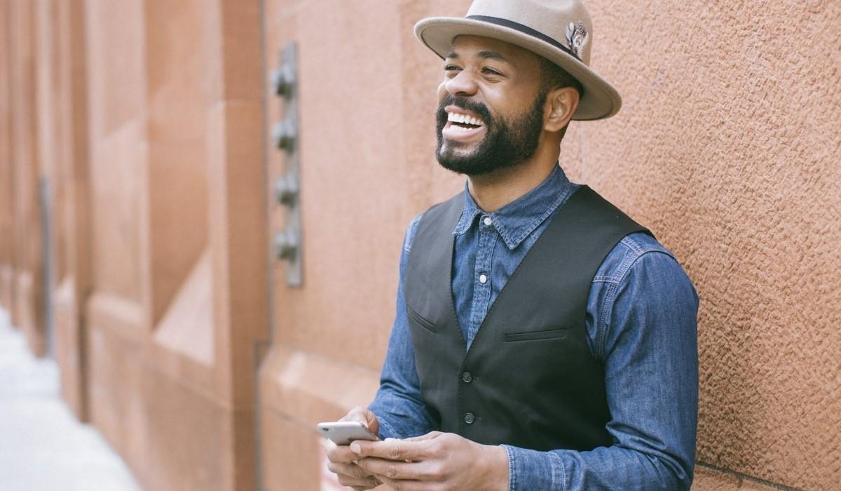 un homme souriant avec son smartphone en main