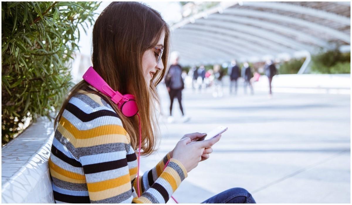 jeune femme assise avec son smartphone en main